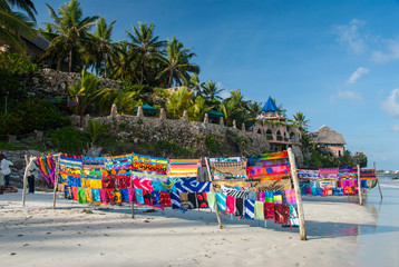 A brightly colored fabrics market on a white sand beach