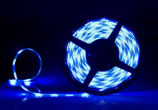 Led strip coil closeup. Diode shining stripe on dark blue background.
