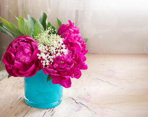 Violet peony flowers in blue vase on wooden table closeup with empty space background.