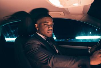 Hispanic businessman inside car at night.