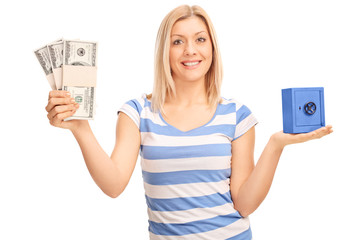 Woman holding money and a small safe