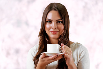 Portrait of young beautiful woman with cup of coffee on pink blurred background