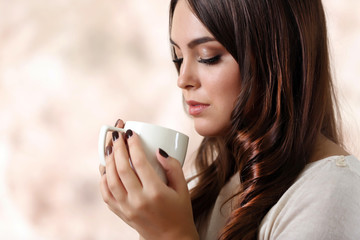 Portrait of young beautiful woman with cup of coffee on pink blurred background, close up