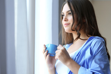 Woman with cup of coffee standing near window in the room