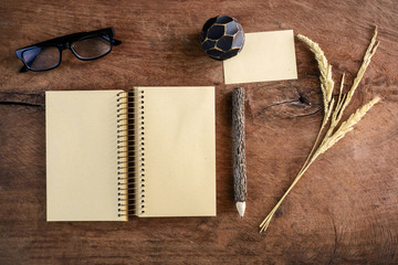 Blank note book with eye glasses and pencil on old wooden desk