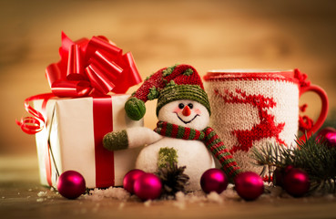 Mug Of Tea Or Coffee. Sweets And Spices. Christmas Decoration with snowman. Wooden Background.