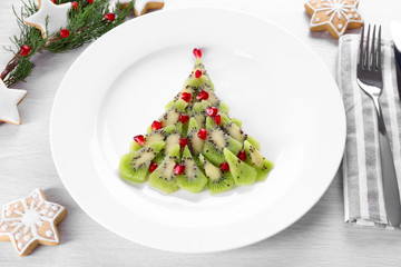 Christmas fir tree made from kiwi, on plate, close up