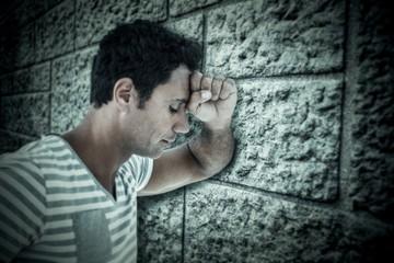 Composite image of upset man leaning on white background
