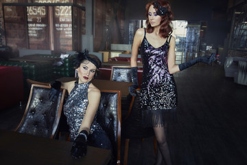 Two girls, models relax in the restaurant.