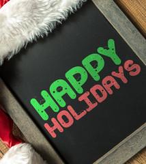 Happy Holidays written on blackboard with santa hat