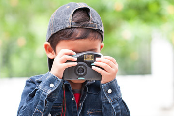 Cute boy using compact camera.