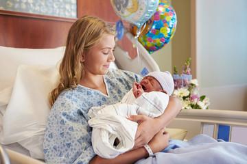 Teenage Girl Holding Newborn Baby Son In Hospital