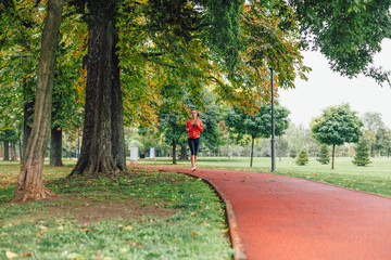 Woman running at the park in autumn