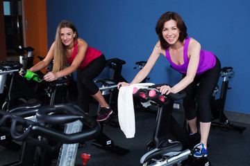 Two smiling women working out on exercise bikes in gym