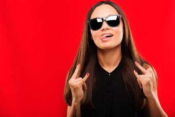 Beautiful young fashion girl having fun on a red background