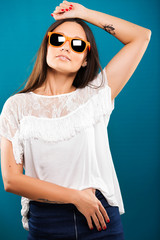 Beautiful brunette girl, with tattoos on her arms, wearing in white blouse, and orange sunglasses, is posing