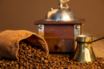 Roasted coffee beans and coffee grinder on dark background