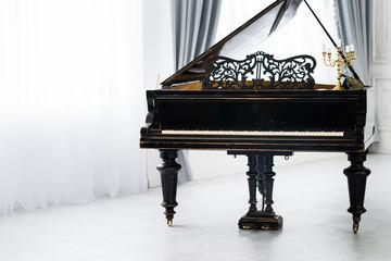 Чёрный старинный рояль стоит в центре красивой светлой комнаты