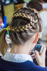 Девушка с красивой косой смотрит на фотографию своей причёски в телефоне