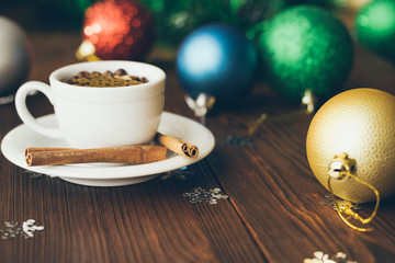 Cup and saucer on a wooden table among Christmas decorations