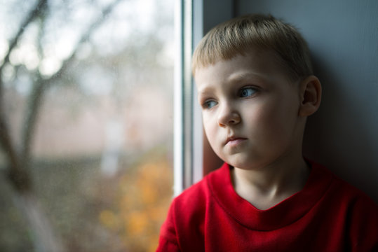 small boy sitting near window and thnking about something