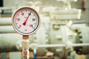 Closeup of a high pressure manometer, measuring natural gas pressure. Pipes and valves in the background. Selective focus.