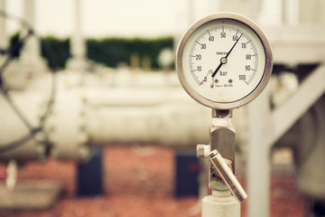 Closeup of a high pressure manometer, measuring natural gas pressure. Pipes and valves in the background. Selective focus