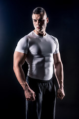 beautiful male athlete in white shirt isolated over black background
