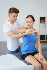 arzt untersucht eine patientin mit schmerzen am arm