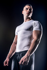 powerful male athlete in white shirt on black background