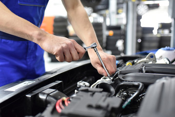 Automechaniker repariert an einem Fahrzeug im Motorraum - closeup // mechanic repairs engine of a car