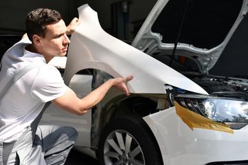 Mechaniker repariert Unfallschaden eines Autos in der Werkstatt - Austausch des Kotflügels im Karosseriebau // car mechanic repair damaged cars in the workshop Wall mural