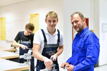 Berufsausbildung in der Metallbranche - Meister und Lehrling am Schraubstock lächeln // Smiling instructor and trainee