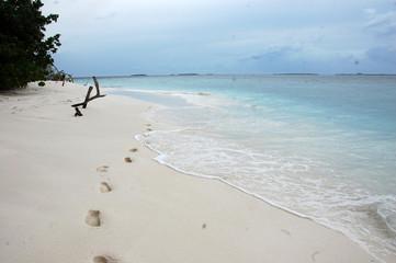 Footsteps at white sand beach Maldives