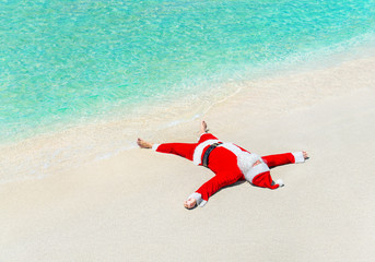 Santa Claus sunbathe on sand at beach, Christmas greeting card