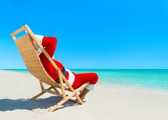 Christmas Santa Claus relaxing on deckchair at ocean tropical beach
