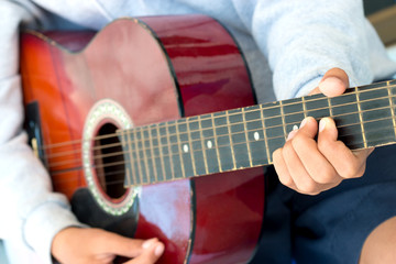 blurred boy's hands playing old acoustic guitar, and teaching