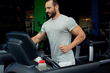 Muscular man running on a treadmill in a fitness club, sport in
