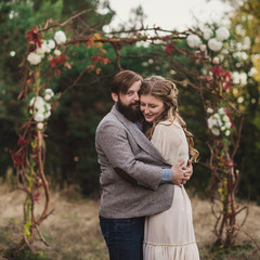 Happy couple stands near wedding arch