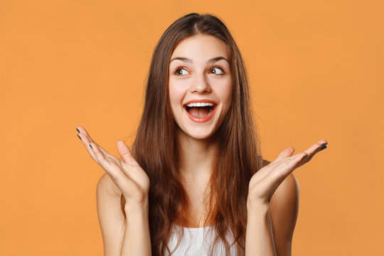 Surprised happy beautiful woman looking sideways in excitement. Isolated on orange background