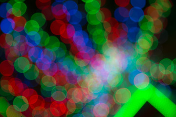 Colorfull background with christmas lights in boken.  Yellow, dark, blue and red light in Bokeh. Defocused. Festive and celebratory background. Disco lights. Laser show