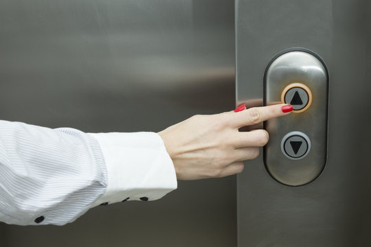 Female hand pressing elevator up button