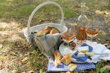 Picnic theme - rose wine, cheese, baguette and nuts outdoors