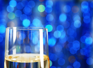 A glass of champagne on blue blurred background