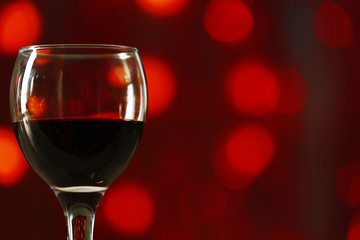 A glass of red wine on blurred lighted background