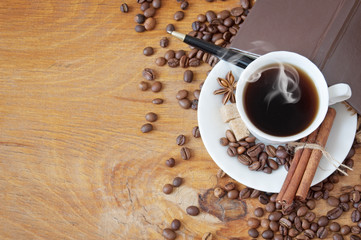 Coffee beans with spice and coffee cup on wooden background