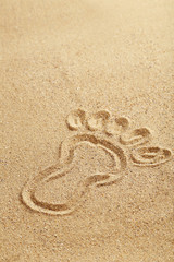 Drawing foot on beach sand