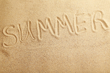Summer handwritten in a beach sand