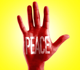 Peace written on hand with yellow background