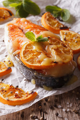 baked salmon steak with oranges closeup on baking paper. Vertical